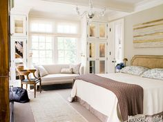 """Frank DelleDonne mixes a laid-back California look with underlying European formality in this New Jersey house. Antiqued mirrors on the built-in closets add mirrors on the built-in closets add """"a little bit of smokiness and mystery"""" to the master bedroom. DelleDonne designed the headboard and covered it in Royal Suede by Edelman Leather. Sferra bedding; Ralph Lauren blanket. Painting by Erin Parish."""