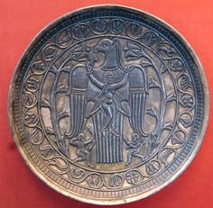 "Magnificent Zoroastrian Art Sassanian Silver Plate with an Eagle grasping a lady in the center with his paws, while the lady is holding some food (perhaps grapes) near the eagle's mouth; Two figures in the bottom of the plate appear as holding a bow and an Ax; Two trees of life surround the scenes; Sassanian period, circa 3rd-7th Century AD - IRAN (now at: Hermitage museum, Russia)  [of ""‎Beautiful Iran‎‏"" page on facebook.]"