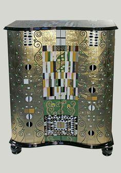 Diese Kommode mit dem Motiv von Gustav Klimt »Schmalwand« ist ein Muss für jeden Kunstliebhaber! Die schöne 2-türige Kommode hat zwei Einlegeböden und dient hervorragend zum Aufbewahren Ihrer Lieblingsstücke und ist gleichzeitig ein echtes Kunstwerk!  Gustav Klimt (1862-1918) kam in einer ärmlichen Umgebung zur Welt. Er stieg dank seiner genialen Begabung zum Malerfürsten der Wiener Gesellschaf...