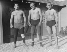 """A picture of (from left to right) Leo Papionis (Greek wrestler from Los Angeles), Ira Dern (world light heavyweight grappling champion), and George Batalis (Las Vegas wrestler), all preparing for the World Championship Wrestling Match at El Patio Open Air Theatre in Las Vegas, May 23, 1929.  Image is part of UNLV Libraries """"Photo"""" digital collection."""
