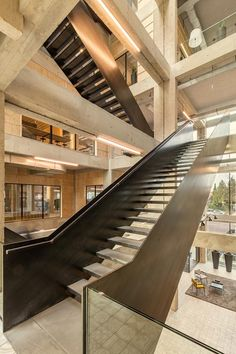 Studioninedots has renovated a 1970s office building in Hilversum, adding a four-storey void crisscrossed by steel staircases.