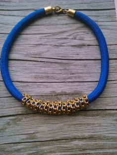 A royal blue climbing rope necklace braided with gold chain.
