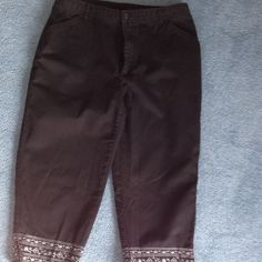 Black capris with detail. Capris have zip front and two front pockets. Belt loops. Side slit at hem and white embroider stitch detail at hem. Gently worn. Field Gear Pants Capris