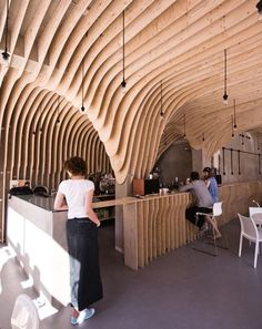 Curved plywood forms an undulating cave-like ceiling around the bar of this coffee shop in Poland. Patches of plaster are visible on the walls, which are intentionally left unfinished. Designed by polish architects xm3.