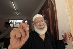 Joyous: A man shows his ink-stained finger after casting his vote at a polling station in Alexandria