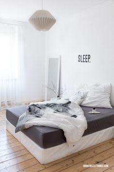 Schlafzimmer in Weiß und Grau mit Origami-Lampe und Boxspringbett