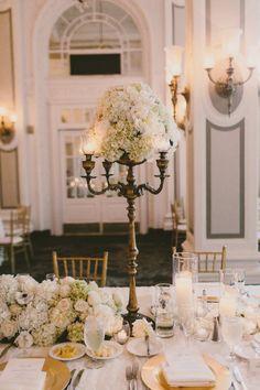 Centro de mesa con candelabros dorados.