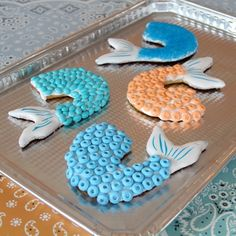 Mermaid Tails Cookies #Disney  Mermaid Tail Cookie Template  Batch of chilled sugar cookie dough (homemade or store-bought)   Flour   Rolling pin   Wax paper   Baking sheet   Cooling rack   Kitchen knife   White cookie icing   Candy necklaces or other small candies  Colored sugar (optional)   Food decorator pens (optional)
