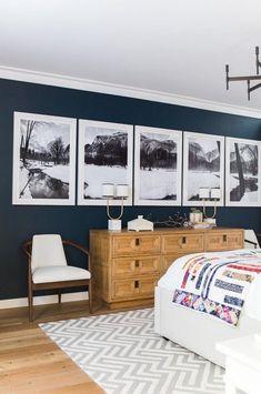 Amazing bedroom with black&white wall art, wood dresser, zigzag rug and light wood floor
