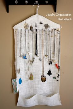 A hanger with some loosely woven fabric hung with some pockets (hand stitched or glued) and you have a jewelry organizer. Also, I am in blog love.