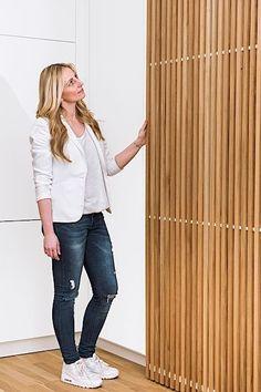 Designérka Martina Pištěláková upozorňuje na posuvný dubový panel, který částečně překrývá nábytkovou stěnu.
