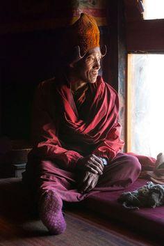Tibetan buddhism monk looking through the window in the dark praying hall in Karsha Gompa by Rafał Leszczyński on 500