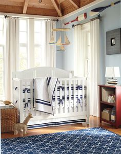 Boys Nursery - Nautical Sails - Pale blue walls and warm wood tones.  Sailboat mobile, decorative oars and other boat inspired accessories; a navy and white palette for the crib bedding and the rug complete the nautical style.  From Pottery Barn for Kids