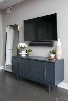A Modern, Master Bedroom Makeover in the City of Chicago Love this gray bedroom dresser with the TV mounted above it. Plus then you can use the top of it to display pretty accessories. Love the lar Modern Master Bedroom, Tv In Bedroom, Master Bedroom Makeover, Bedroom Dressers, Gray Bedroom, Trendy Bedroom, Home Decor Bedroom, Tv Stand In Bedroom, Bed Room