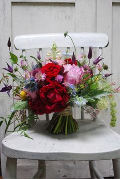 looks like peonies, sea hollies, tulips (i think), scabiosas, billy buttons, bachelors' buttons, and some other stuff