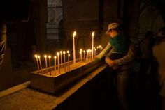 Lighting candles inside The Holy Church of the Sepulchre in Jerusalem, Israel
