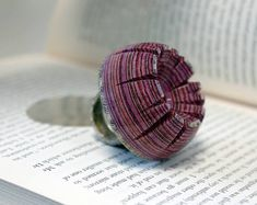 London-based artist Jeremy May gives discarded books a new lease on life with his wearable sculptures. Images and text are harvested from these publications and formed into modern rings, bracelets, necklaces, and more. Their colorfully layered and patterned designs hardly resemble books at all—instead, they appear as lustrous, stylish accessories that mesmerize us with their beautiful curves and shapes. May goes through the same meticulous process to create each piece of jewelry. It begins…