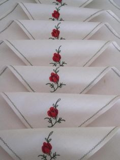 Set of  Ten Embroidered TABLE NAPKINS 25cms x 25 cms Stored over a long period of time and not used. Floral emblem in each corner.