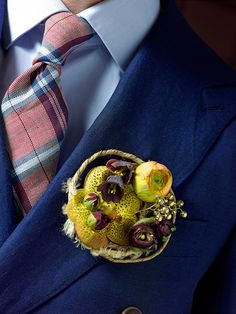 Contemporary, round groom's boutonniere in tones of orange and deep purple, with orchids and ranunculi. By http://valentijnsneek.nl/specialisme/bruidswerk/