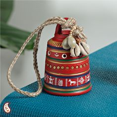 A Beautiful Red Painted Bell beautiful painted terracota bell with sea shells and a hand woven jute string to make a great hanging in your living room.