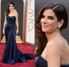 Sandra Bullock brings the movie-star drama we expect from the Oscars red carpet in a midnight-blue Alexander McQueen gown featuring a strapless sweetheart neckline and some award-worthy waterfall draping. Sandy polishes things off with spiraling chestnut waves, smoky eyes and sizable diamond ear cuff from Lorraine Schwartz.