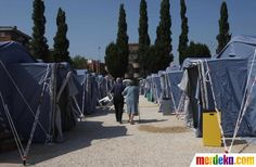 Dua orang berjalan di sebuah tenda pengungsian Medolla, Modena, Italia, Selasa (29/5)