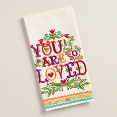 """Show your kitchen decor you care with our sweet, rickrack-trimmed tea towel. Embroidered with bright flowers and the words """"you are so loved,"""" it makes a charming statement for Valentine's Day (or any other day)."""