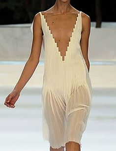 Love the contrast of the plunging geometric neckline and the flowing transition of the hem.