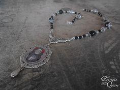 Magnifique collier orné de perles d'un noir profond et de perles argentées délicatement décorées. Acroché à un apprêt argenté, le portrait d'une femme squelette revenue d'entre les morts dans un beau médaillon.