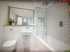 Small bathroom decorating ideas with use white tile bathroom and bathtub shower combo also floating toilet and floating sink with the above plus a large bathroom mirror would conserve bathroom space saver Metro Tiles Bathroom, Large Bathroom Mirrors, Large Bathrooms, Small Bathroom, Bathroom Ideas, Tiled Bathrooms, Bathtub Ideas, Retro Bathrooms, Bathroom Modern