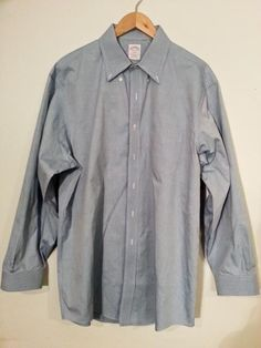 Oxford Style Blue Dress Shirt. Button Down Collar. Standard Cuffs. Overall good condition, but there is a manufactured flaw in the fabric at the shirttail.