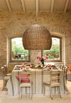 Dining room with stone walls and large wicker lamp