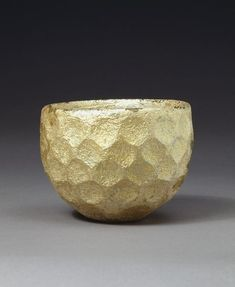 This type of thick-walled glass cup is relatively common. The glass was originally clear with a green tinge. The iridescent patina here is the result of a long period of burial. The surface is cut with circular facets in a honeycomb pattern. When Iran was ruled by the Sasanian dynasty (about AD 224 to631), the techniques used to cut precious and semi-precious stones were also used on glass. (Iran)