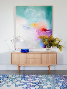 Beautiful large scale Australian art styled perfectly with a big bunch of wattle. That geometric rug is a great choice, picking up the aqua and blue tones from the painting.