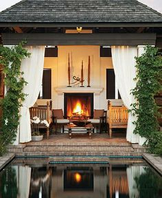 day beds, an outdoor fireplace, and billowing curtains make for a perfect outdoor living space