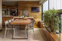 Painel de madeira com churrasqueira a gás, mesa de jantar de madeira da Tora Brasil, cadeiras Play da Dedon na varanda do apartamento da arquiteta Daniella de Barros
