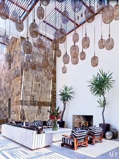 Twine-wrapped lanterns are suspended from the slatted canopy over George Clooney's Baja, Mexico, courtyard, which features a built-in fireplace.