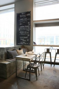 Go all out with concrete on different shades from the floor, booth seating, divider, to the wall. Furnished with metal chairs and wood tabletops.