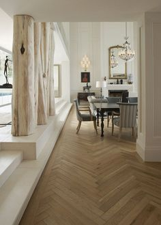 Love the tree trunks mixed with modern furniture! Designers Julian and Trevyn McGowan applied their meticulous eye for detail to the home's interior, from the oak parquet flooring to the striking white-painted Georgian style panelling throughout – an exciting juxtaposition with the modern architecture.