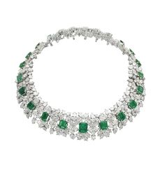 AN IMPORTANT EMERALD AND DIAMOND NECKLACE BRACELETS, BY HARRY WINSTON Set with a graduated line of twenty-three rectangular-cut emeralds each within a pear and brilliant-cut diamond foliate cluster, detaching to form two bracelets, necklace 37.0 cm inner circumference, bracelets 17.5 cm long, in two Harry Winston black suede pouches With maker's mark of Jacques Timey for Harry Winston