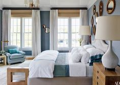 At a Bridgehampton, New York, home designed by Steven Gambrel, overscale 1960s table lamps flank a Gambrel-designed bed dressed with Pottery Barn sheets in a guest room. The vintage rattan mirrors came from a Paris flea market | archdigest.com
