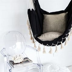 black hammock with cream tassels and gold metallic cushions on white background with ghost chair and coral
