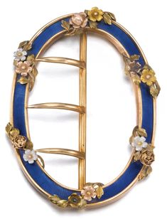 A FABERGÉ THREE-COLOUR GOLD AND ENAMEL BELT BUCKLE, MOSCOW, CIRCA 1895 oval, enamelled in translucent azure blue over sunburst engine-turning, overlaid with sprays of pink, white and yellow gold roses, struck KF in Cyrillic, 56 standard height 7cm, 2 3/4 in.