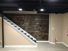 Wood plank wall coming down basement staircase. 1x8x8ft tongue and groove planks with two coats of Minwax Dark Walnut stain.