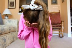 Long wavy hair in ponytail with white wire headband tied in a bow to cover up the hair tie.