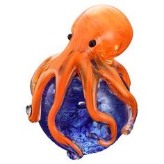 """Blue glass paperweight with an orange octopus accent.   Product: PaperweightConstruction Material: GlassColor: Orange and blueDimensions: 4"""" H x 3"""" Diameter"""