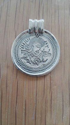 Vedhæng: Bragteat Sølv 240 kr.  30 x 26 mm -  Oprindelig efterligninger af  kejsermedailloner i guld. Nordiske  runer, helligtegn og dyrefigurer kom  til, og efterhånden gik det klare  portræt over i en blanding af  forskellige motiver. De blev båret  som amuletter mod onde magter og viste rigdom.  Der blev fundet over 300 brakteater i Danmark, originalen af dette smykke 1884 i Darum ved Ribe.