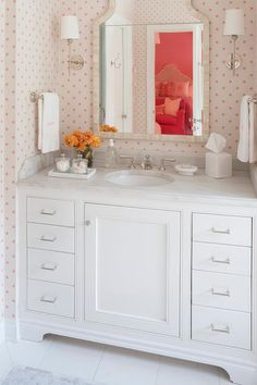 Clad in pink polka dot wallpaper, this white girl's bathroom boasts a Wisteria Moorish Bone Mirror flanked by polished nickel sconces mounted above a white washstand fitted with polished nickel hardware and a white marble vanity top with an oval sink paired with a polished nickel faucet kit as polished nickel towel bars hold white and pink monogrammed towels on facing walls.