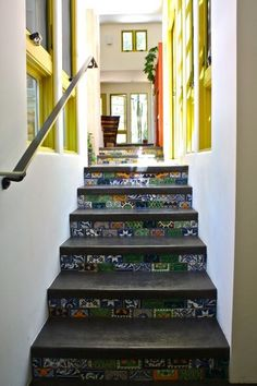 The tile detail on the stair risers adds even more lively color to the home. Svoboda-Spanbock designed the stairs to look like a waterfall when someone is standing at the bottom and looking up. The top has more oranges and yellows — representing the earth — which gradually fade into more greens and blues to represent water.