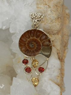 "Handmade Ammonite Fossil pendant accented with faceted Garnet and Citrine gemstones, bezel-set in 925-hallmarked sterling silver. Coordinating bracelet available separately. Length: 2"" Width: 1"""